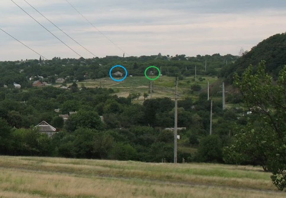 A part of another recreated photograph taken by a local and published by Ukraine@war showing the hill the Panoramio picture was taken from as well as the houses marked by a blue and green circle. The wooden electricity poles aren't in the picture here because they have likely been removed.