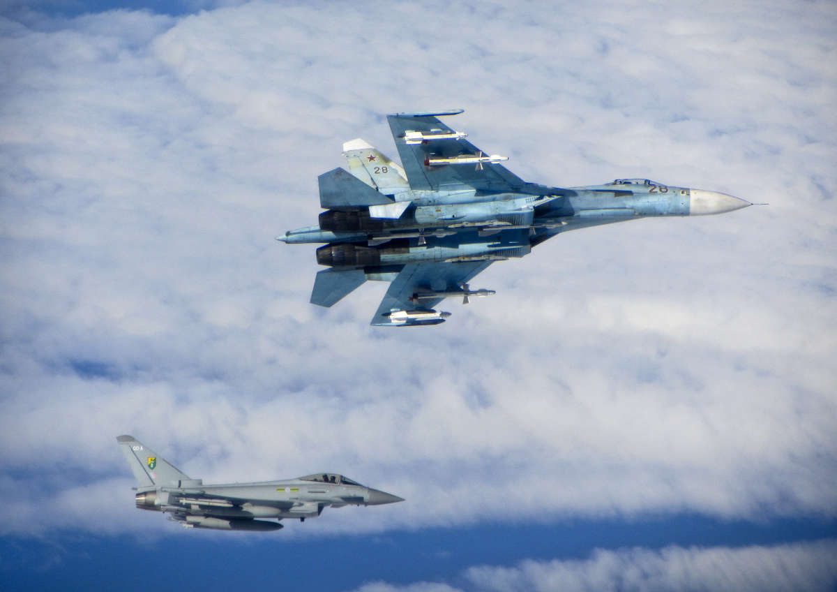 A Russian SU-27 Flanker aircraft banks away with a RAF Typhoon in the background. RAF Typhoons were scrambled on Tuesday 17 June 2014 to intercept multiple Russian aircraft as part of NATO's ongoing mission to police Baltic airspace. The Typhoon aircraft, from 3 (Fighter) Squadron, were launched after four separate groups of aircraft were detected by NATO air defences in international airspace near to the Baltic States. Once airborne, the British jets identified the aircraft as a Russian Tupolev Tu22 'Backfire' bomber, four Sukhoi Su27 'Flanker' fighters, one Beriev A50 'Mainstay' early warning aircraft and an Antonov An26 'Curl' transport aircraft who appeared to be carrying out a variety of routine training. The Russian aircraft were monitored by the RAF Typhoons and escorted on their way. The Typhoon pilots involved in the operation were Flight Lieutenant (Flt Lt) Mark Long of 29 (Reserve) Squadron (the Typhoon operational training unit) and a French Air Force exchange pilot Commandant Marc-antoine Gerrard who is currently attached to 1(Fighter) Squadron.