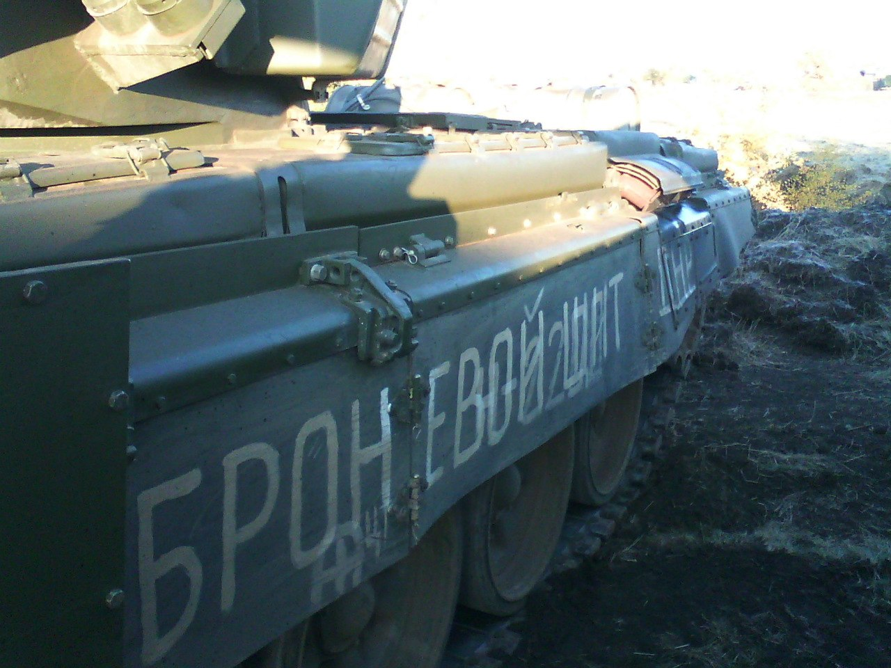 "The same T-72B3 tank numbered 830, but with ""ARMORED SHIELD OF THE DNR"" on the left side. Archive / Original"