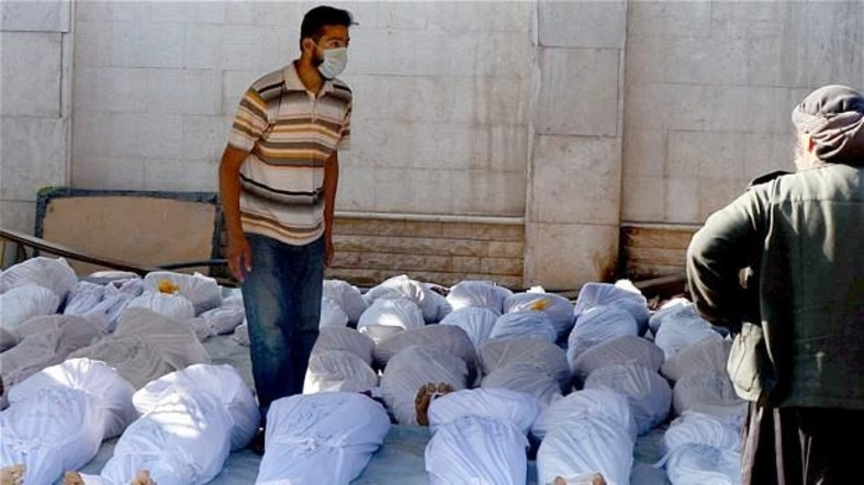 A rescue worker stands amid rows of dead bodies which had suffered sarin exposure. Ghouta, Damascus, August 21, 2013