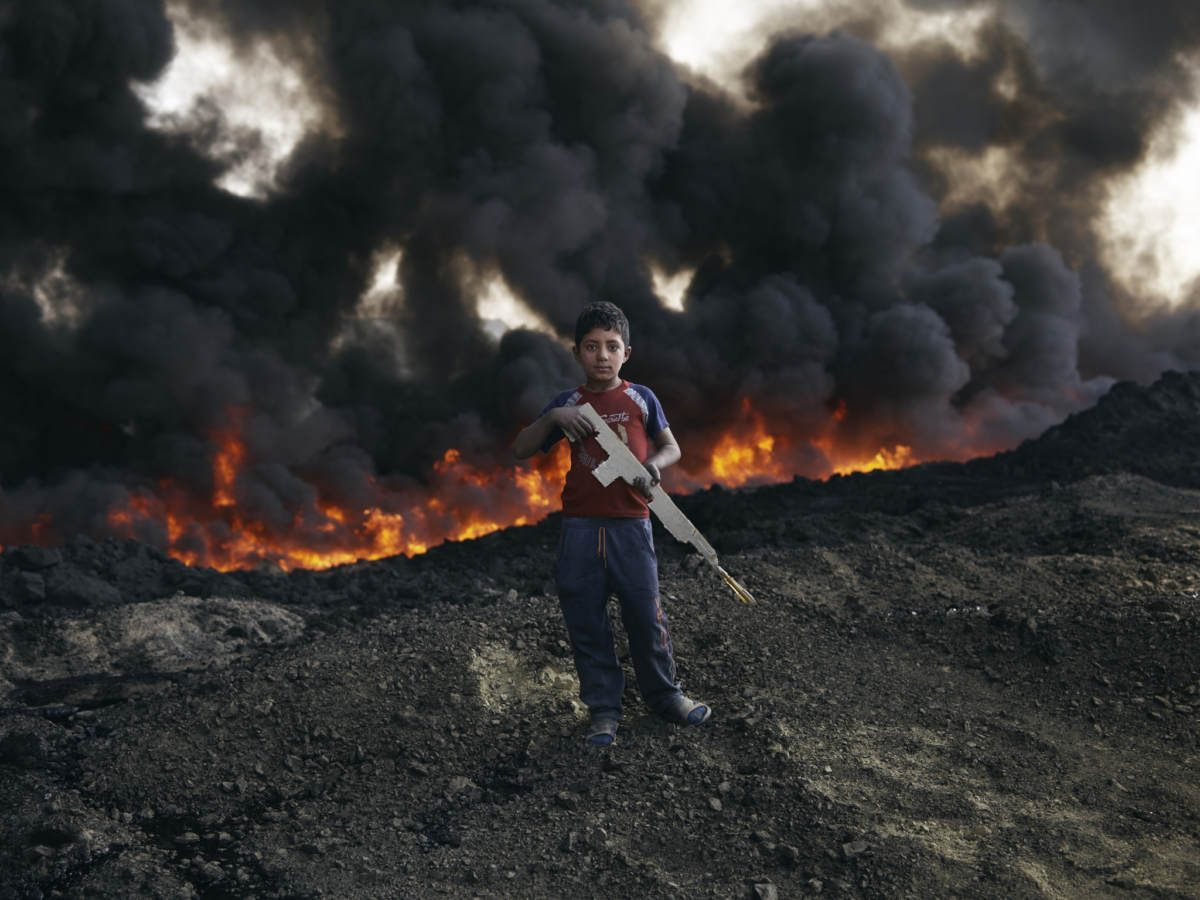Zaer Ibrahim*, 8 plays by the burning oil fields in Qayyarah. Photo by Joe L. for Oxfam