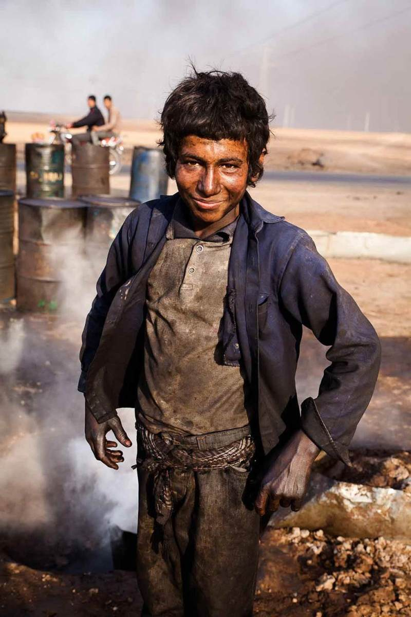 Young boy working at makeshift oil refinery in Hasakah, Syria, 2014