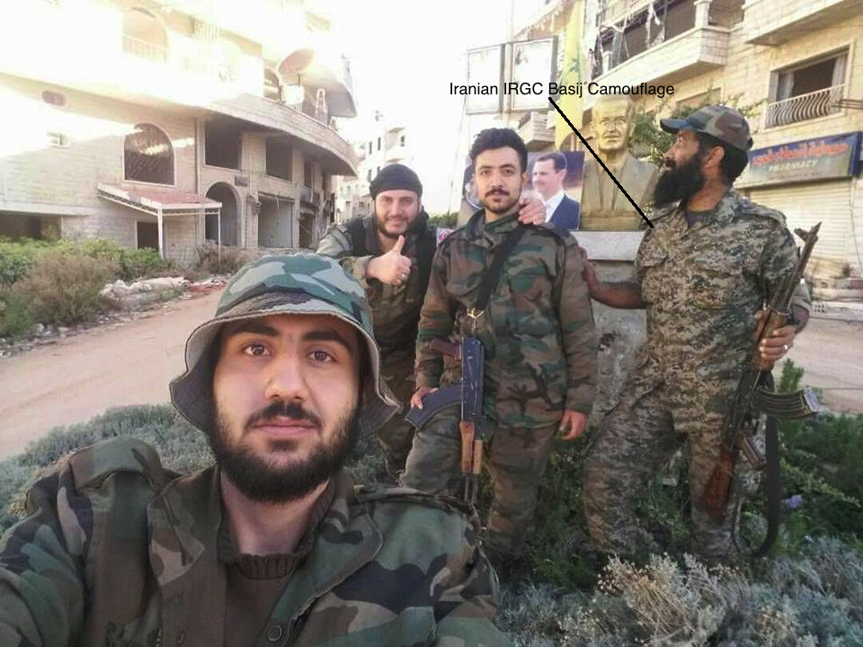 The unidentified combatant on the right is likely wearing Iranian IRGC Basij camouflage
